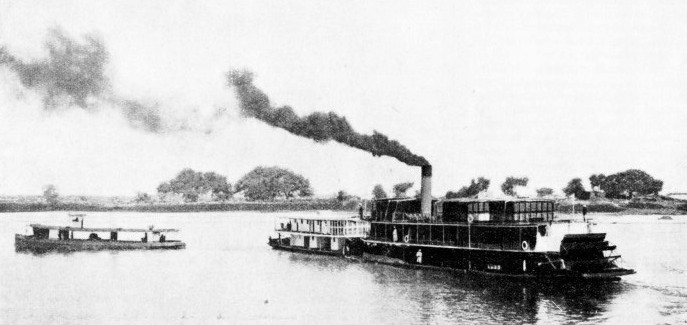 A PASSENGER BARGE being pushed ahead by a Sudan Government passenger stern-wheeler on the River Nile