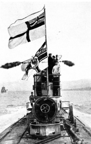 HANDED OVER TO THE BRITISH, this German submarine is flying the White Ensign above the German Ensign