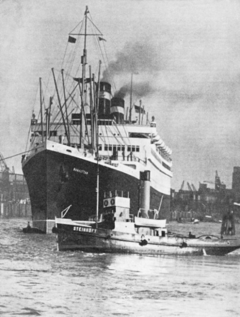 "The ""Manhattan"" towers above a tug"
